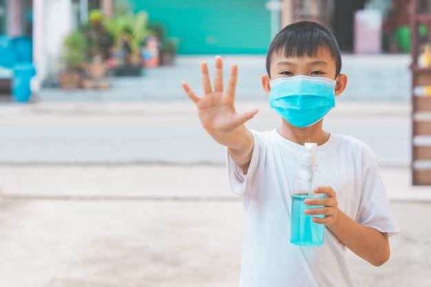 Kinderen die een masker dragen en alcoholgel vasthouden om het coronavirus of het covid-19-virus te doden en hun hand niet naar huis te laten gaan