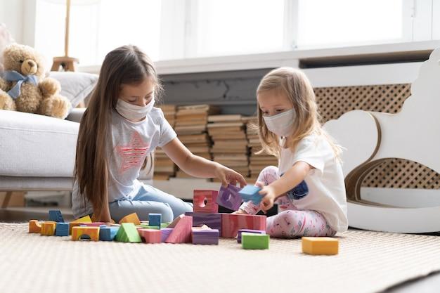 Kinderen die een masker dragen om covid-19 te beschermen, blokspeelgoed spelen in de speelkamer. blijf thuis in quarantaine voor preventie van een pandemie van het coronavirus