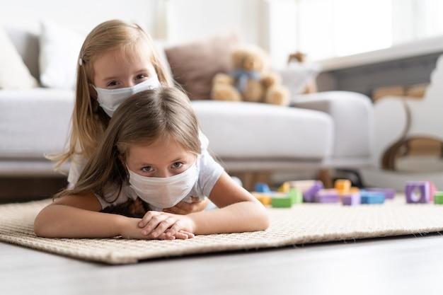Kinderen die een masker dragen om covid-19 te beschermen, spelen in de woonkamer. blijf thuis in quarantaine voor preventie van een pandemie van het coronavirus