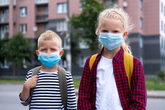 Kinderen die een masker en rugzakken dragen, beschermen en beschermen tegen het coronavirus voor terug naar school. broer en zus gaan naar school nadat de pandemie voorbij is.