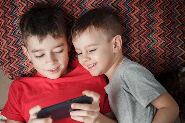 Kinderen die een mobiele telefoon spelen