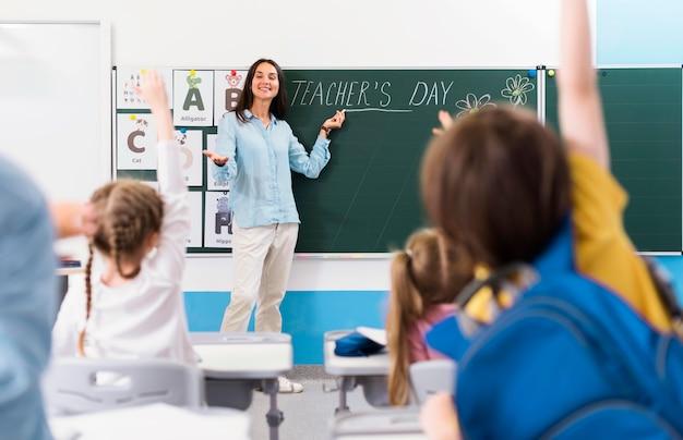 Kinderen die een vraag van hun leraar willen beantwoorden