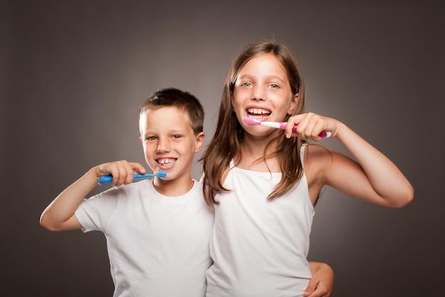 Kinderen die haar tanden op een grijze achtergrond borstelen