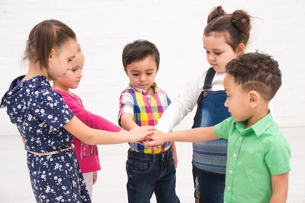 Kinderen die hand in groep houden