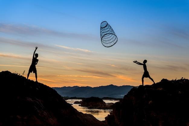 Kinderen die hulpmiddel voor visserij in de zonsondergang delen.