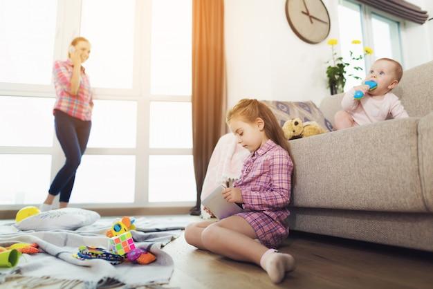 Kinderen die in ruimte terwijl mamma sprekende telefoon spelen.