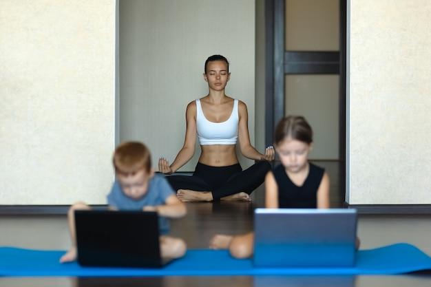 Kinderen die laptops gebruiken en vrouw die yoga doen