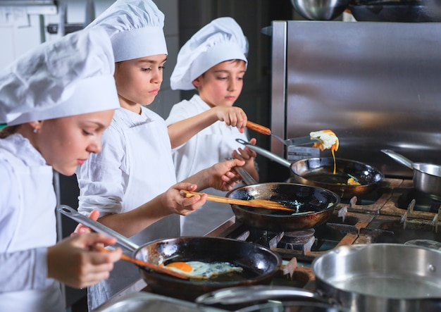 Kinderen die lunch in een restaurantkeuken koken.