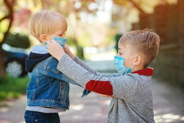 Kinderen die medisch gezichtsmasker in openlucht dragen. de jongen helpt zijn jongere broer een masker op zijn gezicht te zetten.
