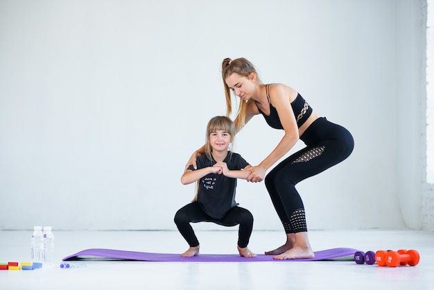 Kinderen die oefenen zijn bezig met gymnastiek en yoga met leraar