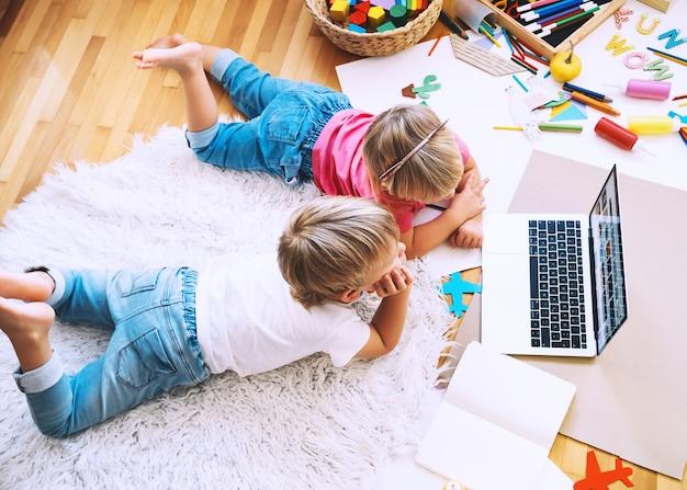 Kinderen die online computertechnologie gebruiken om creatief te tekenen of te knutselen