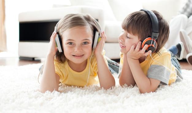 Kinderen die op de vloer met hoofdtelefoons spelen
