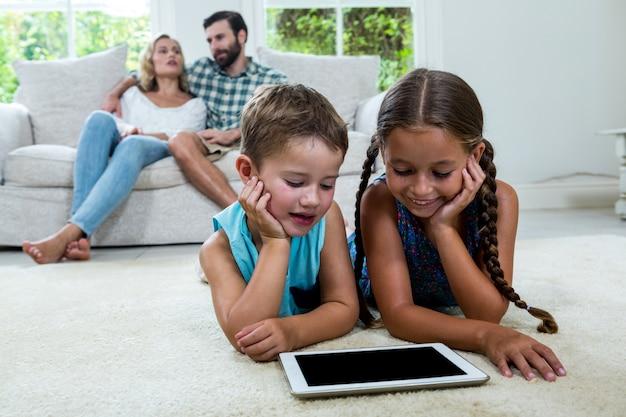 Kinderen die op het digitale tabletscherm letten terwijl ouders op achtergrond