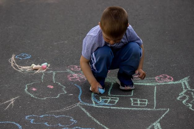 Kinderen die op het huis van de asfaltfamilie trekken. selectieve focus