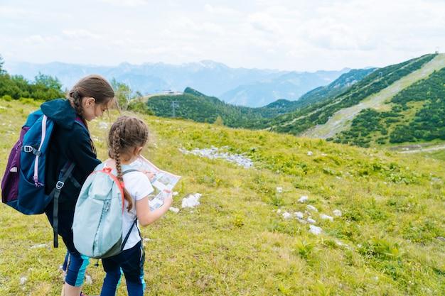 Kinderen die op mooie de zomerdag wandelen in de bergen die van alpen oostenrijk op rots rusten. kinderen kijken naar kaart bergtoppen in de vallei. actieve gezinsvakantie met kinderen. buitenplezier en gezonde activiteit