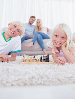 Kinderen die op tapijt het spelen schaak liggen