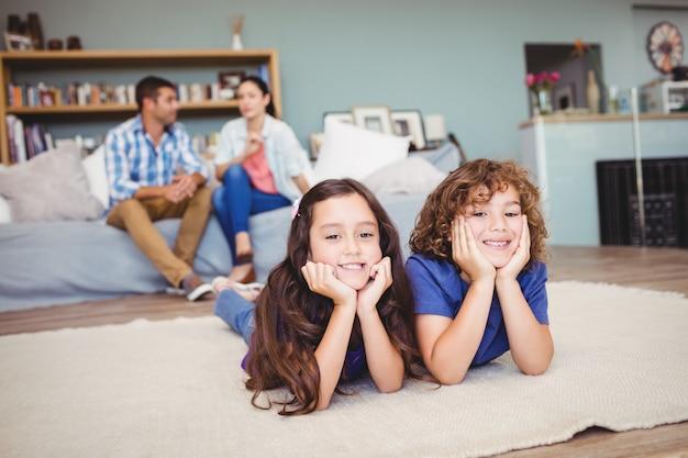 Kinderen die op tapijt liggen terwijl ouders het zitten