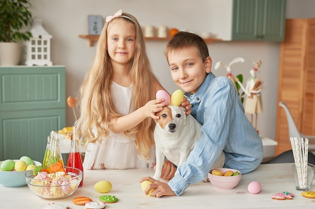 Kinderen die paaseieren houden bij de keuken op een hond