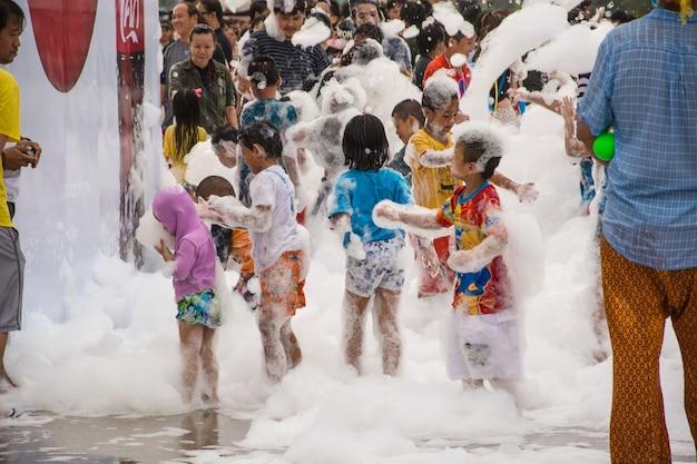 Kinderen die schuim spelen bij songkran-festival in bangkok