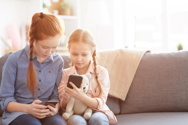 Kinderen die smartphones thuis gebruiken
