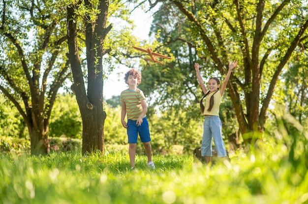 Kinderen die stuk speelgoed vliegtuig in park spelen