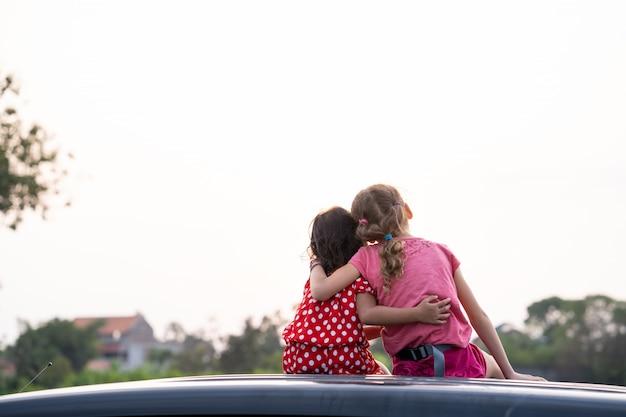Kinderen die van zonsondergang genieten terwijl het zitten bovenop de auto