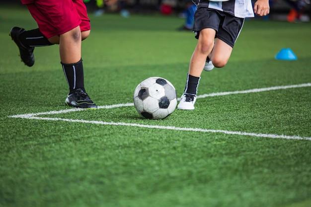 Kinderen die voetbaltactieken spelen op grasveld met voor opleidingsachtergrond kinderen trainen in voetbal
