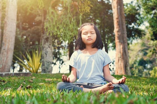 Kinderen die yoga op gras met zonneschijn in het park doen
