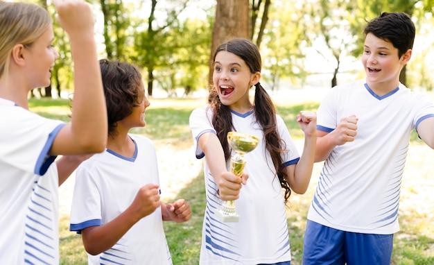 Kinderen die zegevieren na een wedstrijd voetbal