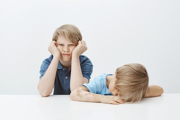 Kinderen die zich vervelen, willen spelen in plaats van huiswerk te maken. portret van onverschillige sombere broerzitting met broer of zus