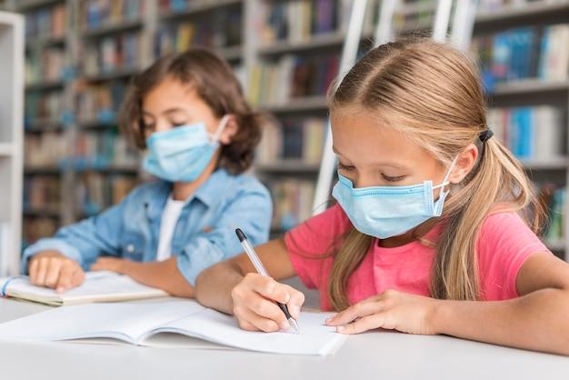 Kinderen doen huiswerk terwijl ze gezichtsmaskers dragen