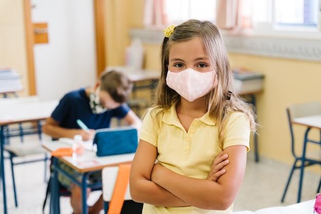 Kinderen doen hun huiswerk in de schoolklas met maskers tijdens de covid-pandemie.