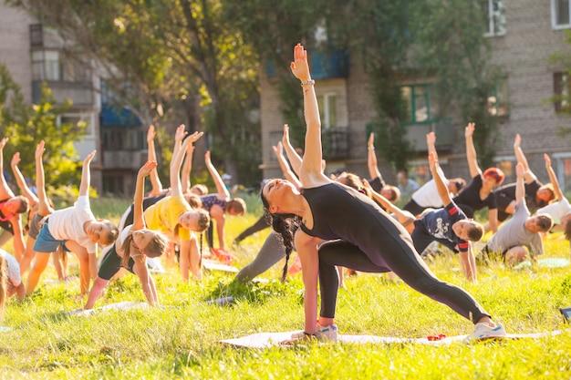 Kinderen doen yoga met een outdoor trainer.
