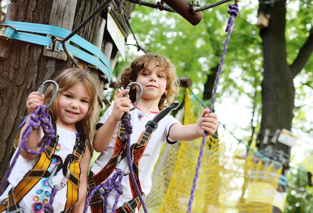 Kinderen - een jongen en een meisje in het touwpark passeren obstakels