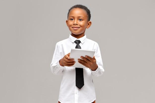 Kinderen, elektronische apparaten en gadgets concept. slimme zelfverzekerde afrikaanse leerling in uniform poseren geïsoleerd met draagbare touchpad-computer in zijn handen, surfen op internet of online winkelen