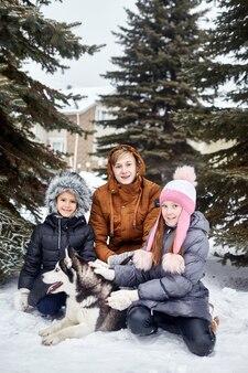 Kinderen en een hond zitten in de sneeuw