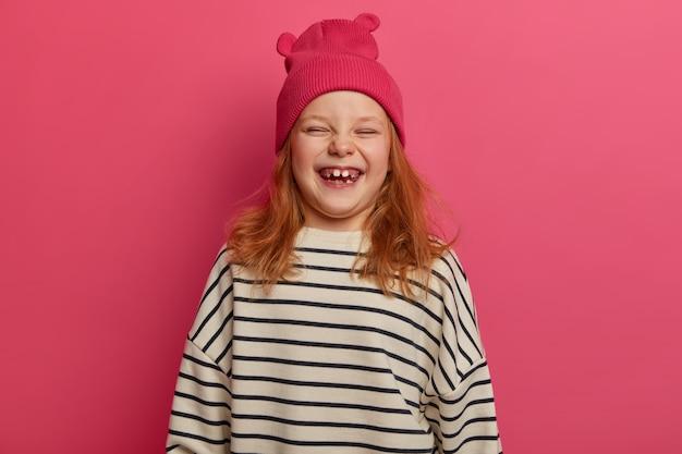 Kinderen en geluk concept. blij roodharig meisje lacht uit iets grappigs, draagt roze hoed met oren en losse gestreepte trui, glimlacht vrolijk, heeft ontbrekende tanden, modellen binnen.