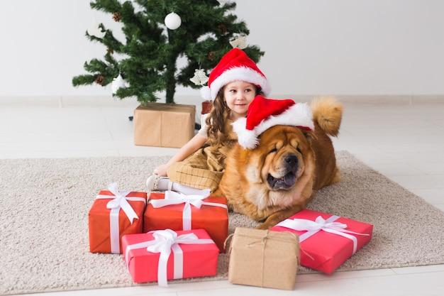 Kinderen en huisdier concept - schattig meisje met chow dog zit in de buurt van de kerstboom. prettige kerstdagen en fijne feestdagen.
