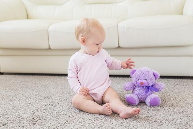 Kinderen en jeugdconcept - klein babymeisje dat op de vloer zit