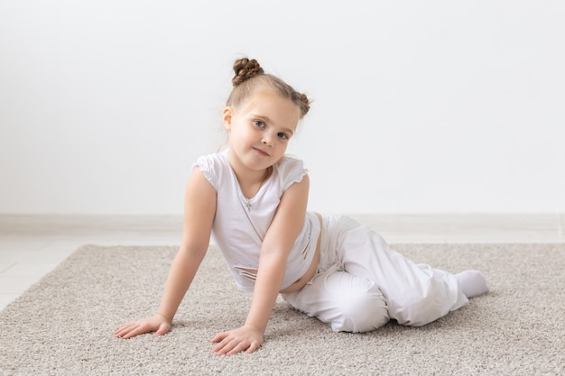 Kinderen en kinderen concept - klein kind meisje gekleed in wit overhemd zittend op de vloer met doordachte gezicht.