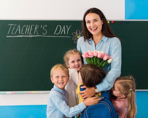 Kinderen en leraar die de dag van de leraar vieren