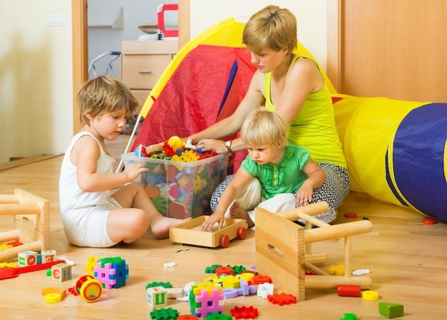 Kinderen en moeder die speelgoed verzamelen
