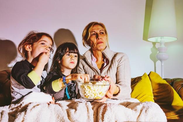 Kinderen en moeder films kijken met popcorn