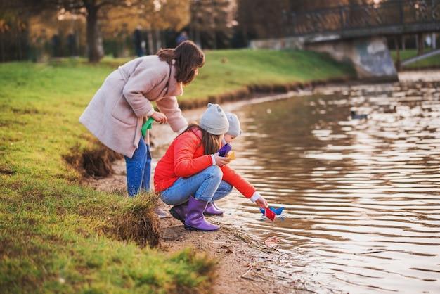 Kinderen en moeder spelen met papieren boten in het meer