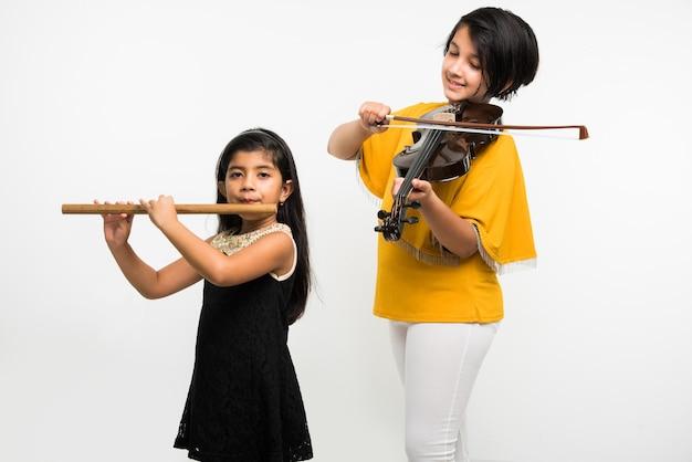 Kinderen en muziek concept - schattige kleine indiase kinderen die muziekinstrumenten spelen als een team of band, op witte achtergrond