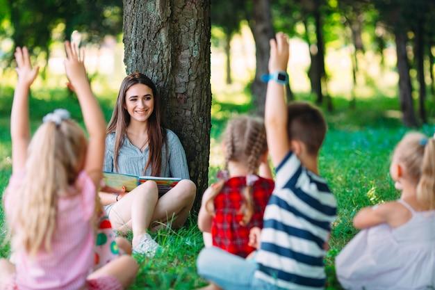 Kinderen en onderwijs, jonge vrouw op het werk als boek van de opvoedingslezing aan jongens en meisjes in park.