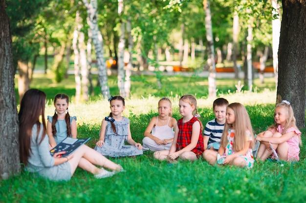 Kinderen en onderwijs, jonge vrouw op het werk als opvoeder leesboek voor jongens en meisjes in het park