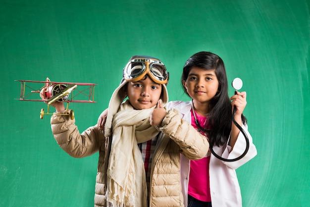 Kinderen en onderwijsconcept - kleine indiase jongen en meisje poseren voor groen krijtbord in pilootkostuum en dokterskostuum met stethoscoop, staande over groene schoolbordachtergrond