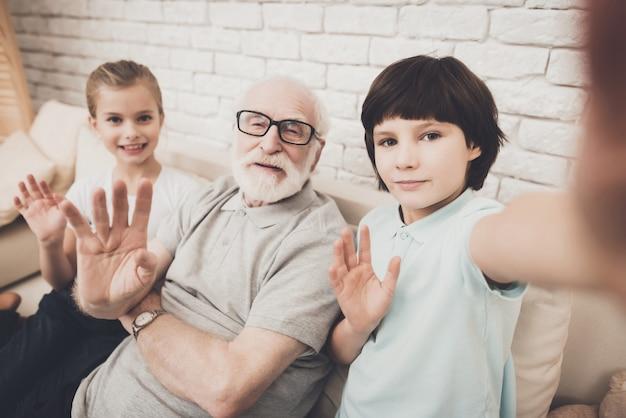 Kinderen en opa voeren videogesprek met zwaaiende handen.