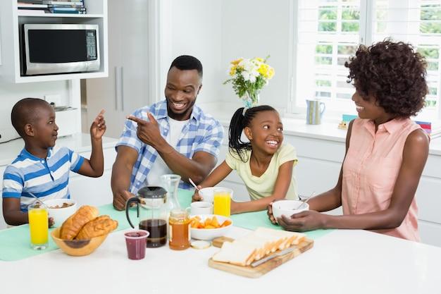 Kinderen en ouders ontbijten op tafel thuis